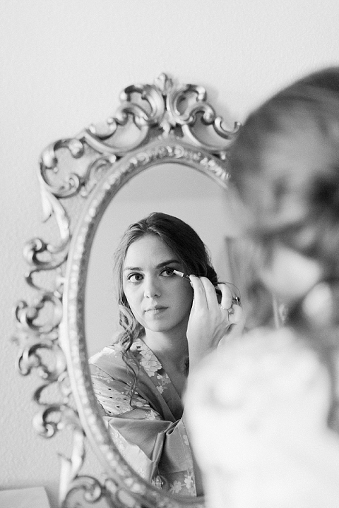 Bride getting ready in ornate mirror