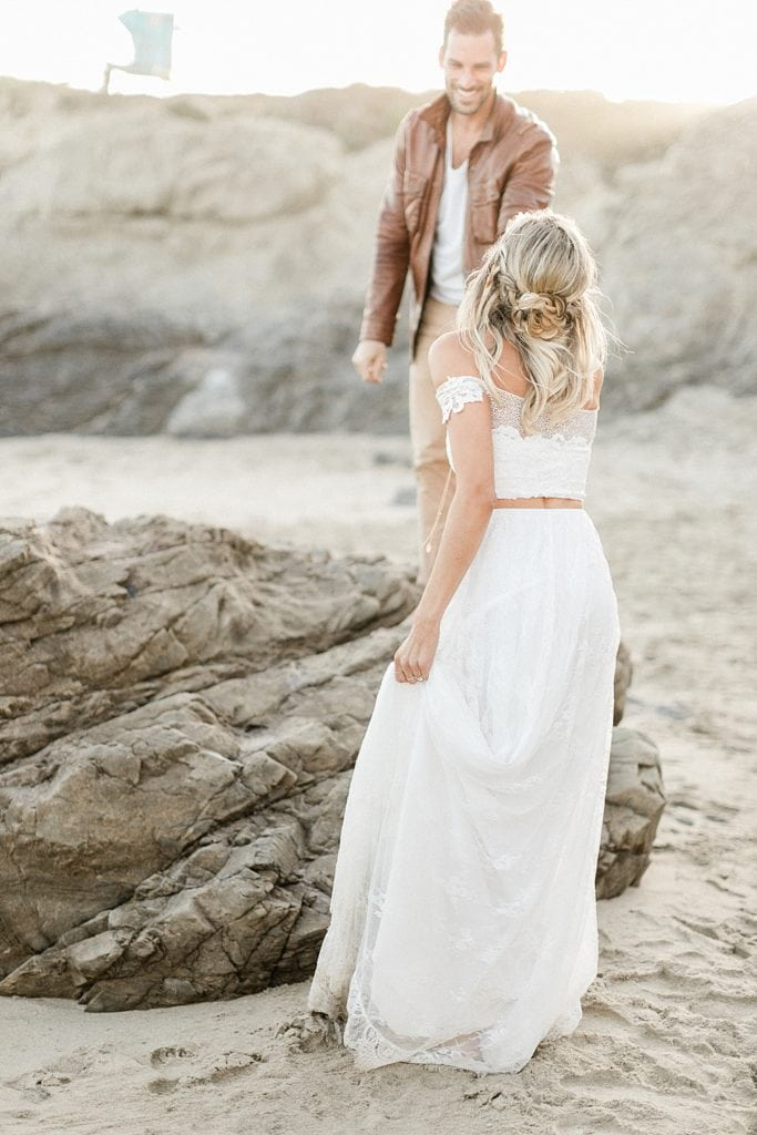 Groom helping bride climb a rock at their Leo Carrillo State Beach Elopement in Malibu, CA